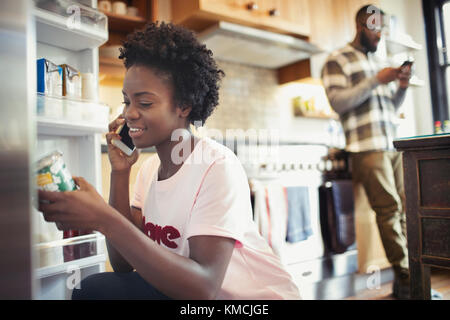 Woman talking on smart phone, reading label on jar in refrigerator in kitchen - Stock Photo