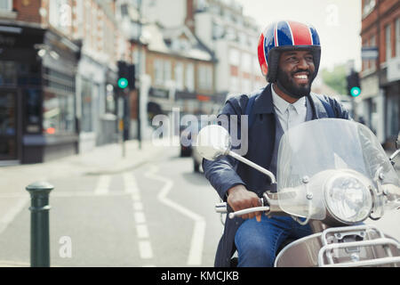 Smiling young businessman in helmet riding motor scooter on urban street - Stock Photo