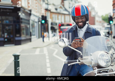 Smiling young businessman in helmet on motor scooter texting with cell phone on urban street - Stock Photo