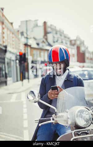 Smiling young businessman in helmet on motor scooter, texting with cell phone on urban street - Stock Photo