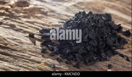 Pile of black lava salt on wooden table. Closeup view. - Stock Photo
