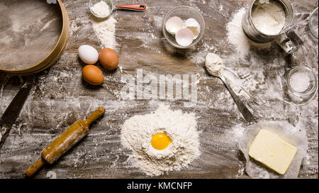 Preparation of the dough. Flour with egg and other ingredients . On a wooden table.  Top view - Stock Photo