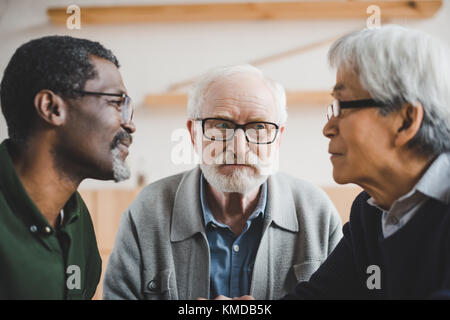 senior friends playing staring contest - Stock Photo