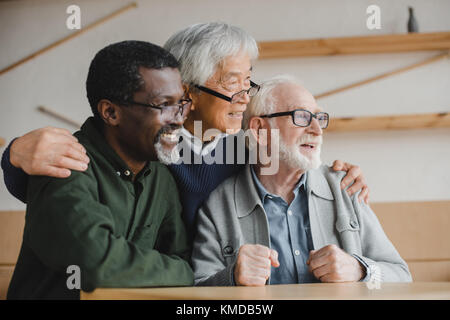 senior friends embracing and looking away - Stock Photo