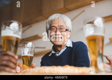 senior asian man in bar with friends - Stock Photo