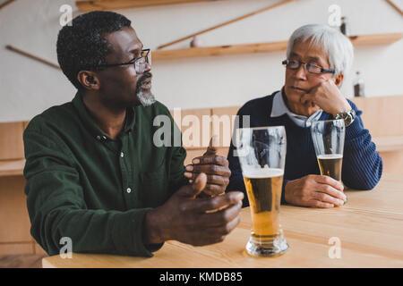 senior friends drinking beer - Stock Photo