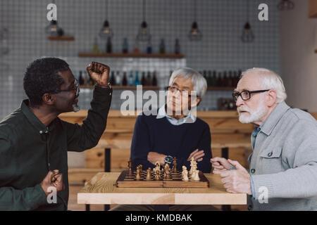 senior friends playing chess - Stock Photo