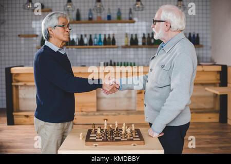 senior men playing chess - Stock Photo