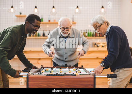 senior friends playing kicker - Stock Photo