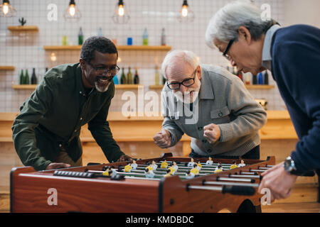 senior friends playing table football - Stock Photo