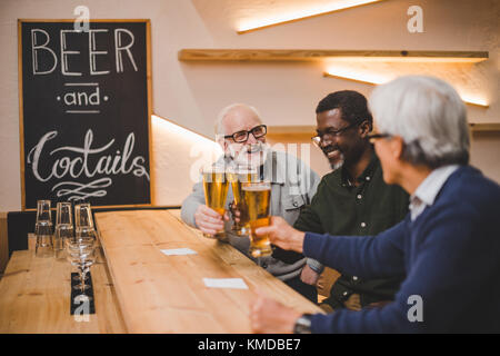 senior friends drinking beer together - Stock Photo