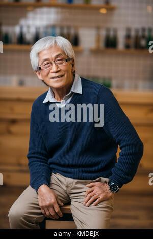 senior asian man in bar - Stock Photo