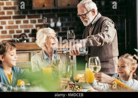 senior man pouring wine for woman - Stock Photo