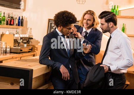 businessmen drinking whiskey in bar - Stock Photo