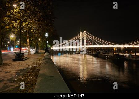 albert bridge in Chelsea looking East at night with Chelsea Embankment - Stock Photo