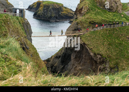 Visitors crossing the famous 'Carrick-a-Rede' bridge on the Causeway coast, Northern Island - Stock Photo