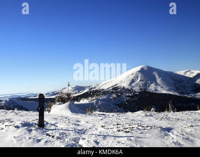 Snowboard in snow and snow-capped mountains at sun cold morning. Mount Petros (Chornohora) at background, view from - Stock Photo