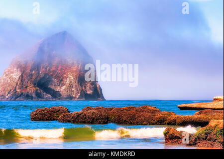 Waves roll into the intertidal rocks as the fog lifts revealing Haystack Rock in Pacific City, on the Oregon coast. - Stock Photo