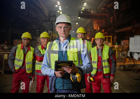 Portrait confident supervisor and steelworkers in steel mill - Stock Photo