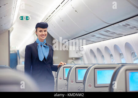 Portrait smiling,confident female flight attendant on airplane - Stock Photo