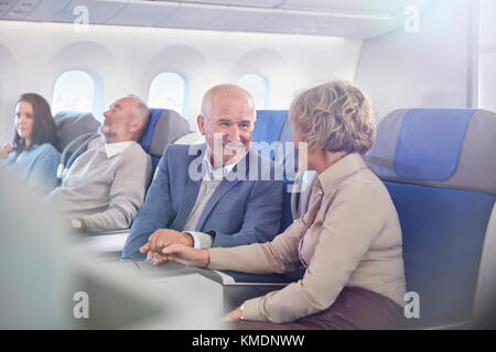 Affectionate mature couple holding hands on airplane - Stock Photo