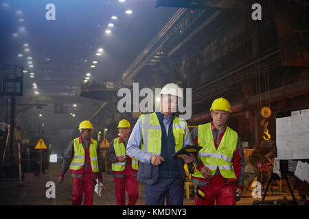 Supervisor and steelworkers walking and talking in steel mill - Stock Photo