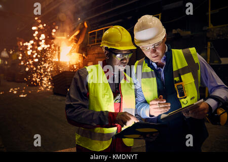 Steelworkers using digital tablets in steel mill - Stock Photo