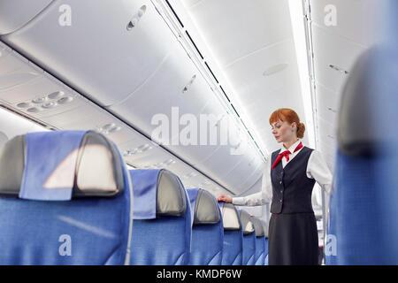 Female flight attendant on empty airplane - Stock Photo