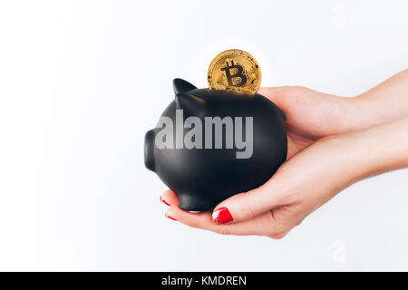 Woman's hands with bitcoin in piggy bank - Stock Photo