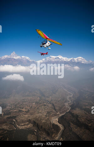 Ultralight trike and plane fly over Pokhara and Annapurna region. Machapuchare or fishtail and Himalayas on the - Stock Photo