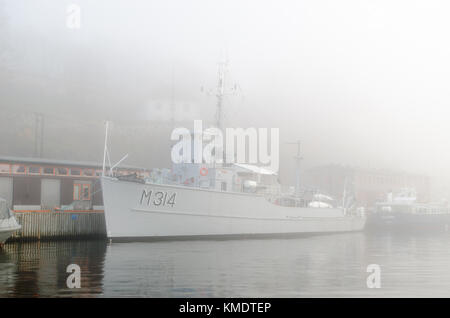 Old retired ex-navy minesweeper in heavy fog mooring in Pipervika bay in Oslo harbour. Late autumn/early winter, - Stock Photo