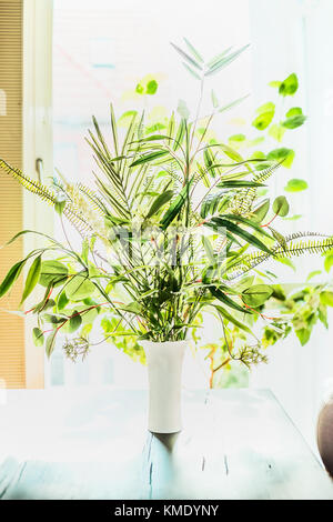 Lovely plants bunch in vase on table at window background. Florist arrangements with variety of green tropical plants.Home - Stock Photo