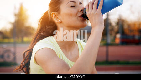 Beautiful female jogger tired after running - Stock Photo