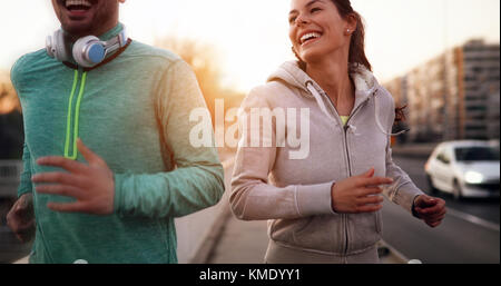 Young fitness couple running in urban area - Stock Photo