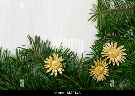 top view of fir christams branches and handmade stars made of straw on a white wooden background - Stock Photo