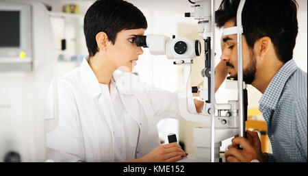 Woman doing eye test with optometrist in eye sight clinic - Stock Photo