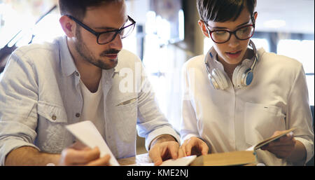 Portrait of students studying in bookstore together - Stock Photo