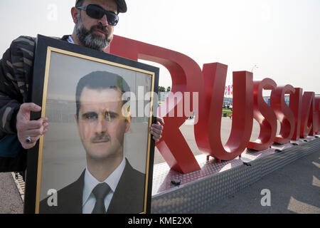 The man holds a portrait of President Bashar Assad near the inscription 'Russia 2018' in the Olympic Park of Sochi, - Stock Photo