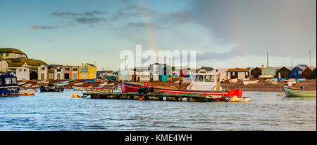 A colourful panoramic of 'life on the estuary' showing moored boats and a variety of beach huts and buildings on - Stock Photo