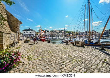 A couple walk along the cobblestone roads at the old pier in Honfleur France with sailboats and flowers on a sunny - Stock Photo