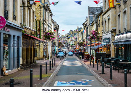 The long, one way Rue Saint-Jean, the main street full of cafes and shops in the Normandy city of Bayeux, France - Stock Photo