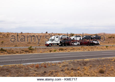 Semi-tractor pulling car hauler trailer on interstate in southeasterrn Arizona, USA, driver visible in cab - Stock Photo