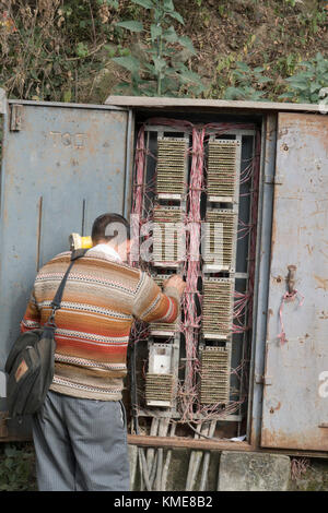 Telecommunications technician works on phone lines in street telephone wiring box at Mcleod Ganj India - Stock Photo