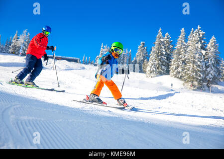 Happy little boy skiing with his father on ski holiday in Alps. - Stock Photo