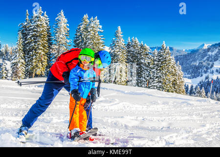 Happy little boy having fun with his father on ski holiday in Alps. - Stock Photo