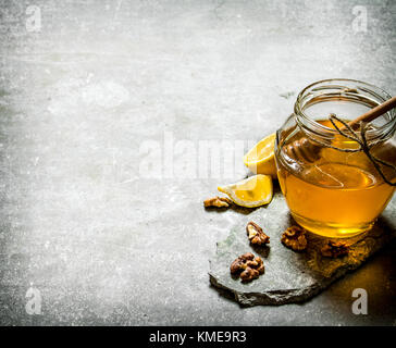 Natural honey in a jar , lemon and walnuts. On a stone background. - Stock Photo