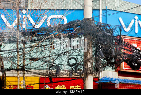 A tangled mess of electric and telephone wires top tall poles through much of central Xian,giving rise to questions - Stock Photo