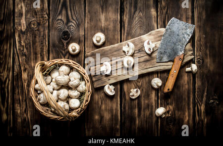 Sliced fresh mushrooms old hatchet. On wooden background. - Stock Photo