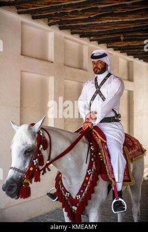 Man in traditional Arabic clothing riding horse at Souq Waqif,Doha,Qatar - Stock Photo