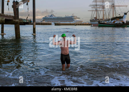 man in swimming trunks flexing muscles while standing in water, Dolphin Club, San Francisco, California, USA - Stock Photo